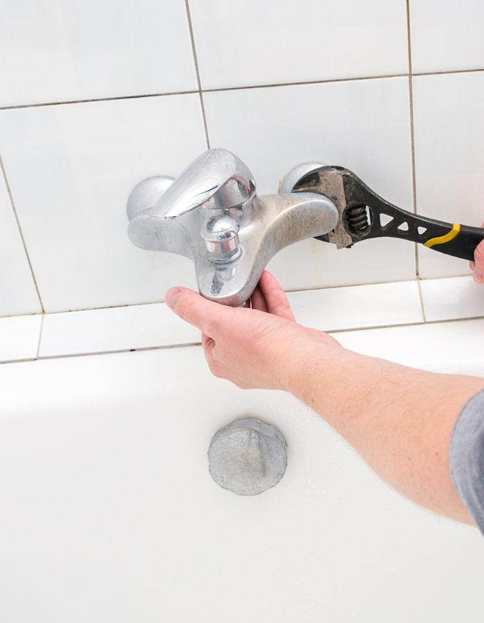 living_water_mechanical_kelowna_plumbing_man_switching_out_shower_faucet